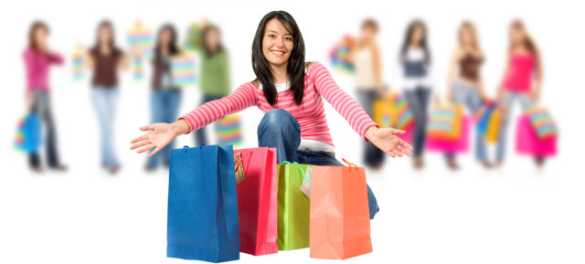 group of happy girls or women smiling and carrying shopping bags isolated over a white background